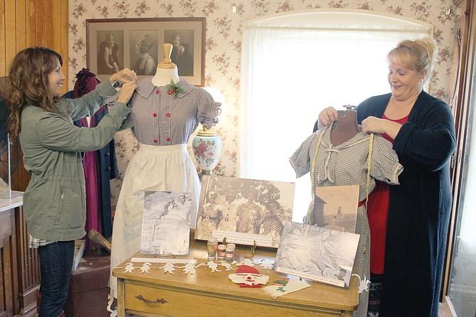 Sunnyside Museum Board members Liz Martinez and Heidi Van Boven adjusts the mannequins wearing house dresses typical of the depression years.