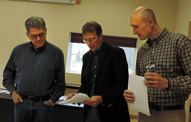 Co-convenors Ken Bailey, left, and Mark Thomas, right, talk with Jim Jakes of the Oregon Solutions office prior to Tuesday's Food Security Coalition signing ceremony at the FISH community room in Hood River. Kirby Neumann-Rea photos