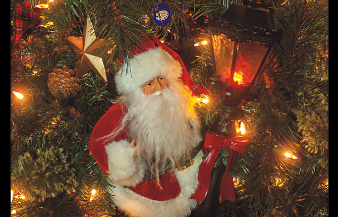 """Santa peers past a lamp post on """"The Giving Tree,"""" donated for the Festival of Trees by the Honald Family in memory of Gary Honald."""