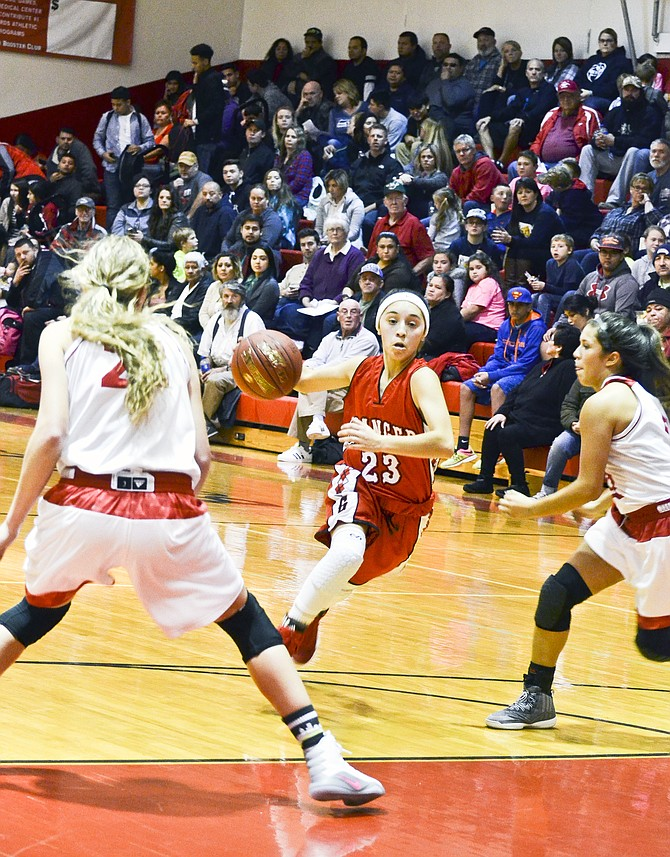 Alexis Castro of the Spartans drives the ball into the paint as Prosser's Brooke Wheeler and Asia Olivarez defend the basket.