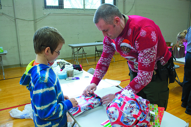 """Polk County Sheriff Deputy Josh Brooks helps Walter Manley wrap presents for his family purchased during the annual """"Shop with the Sheriff"""" event on Saturday."""