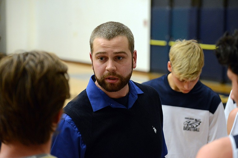 CHRISTOPHER DIRKS (above), first-year head coach of the HRV boys varsity basketball team, speaks with players before the start of Friday's home debut against Redmond. The team rolled the Panthers in a 29-point victory.