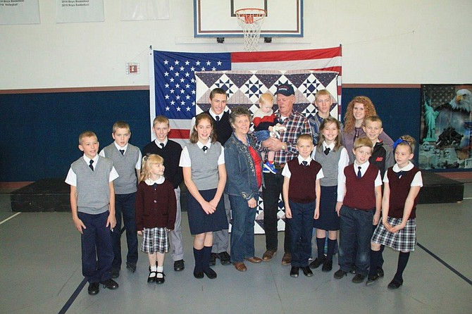 Pictured are Virgil and Donna Wassmuth with 14 of their 17 grandchildren with the Quilt of Valor in the background.