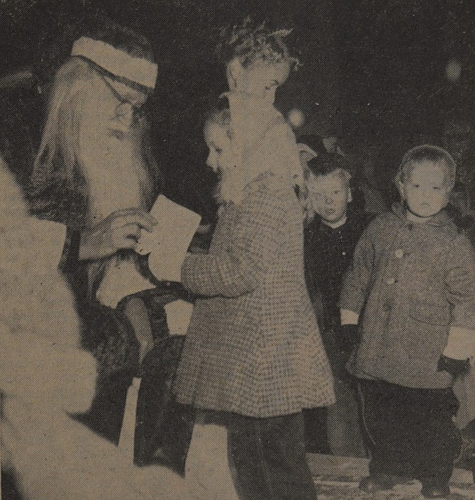 December 13, 1956 — Santa Claus receives a letter from five-year-old Sandra Butterfield which lists all the things she wants for Christmas. Sandra, daughter of Mr. and Mrs. Bill Butterfield, handed Santa the letter shortly after he arrived in Hood River Friday night. About 75 youngsters visited with Santa and Miss Snow Queen, Jo Anne Harms, pictured to the right of Santa. Candy canes were given by firms participating in the merchants' committee program. Choral groups from Wy'east and Hood River sang carols before and during Santa's visit.