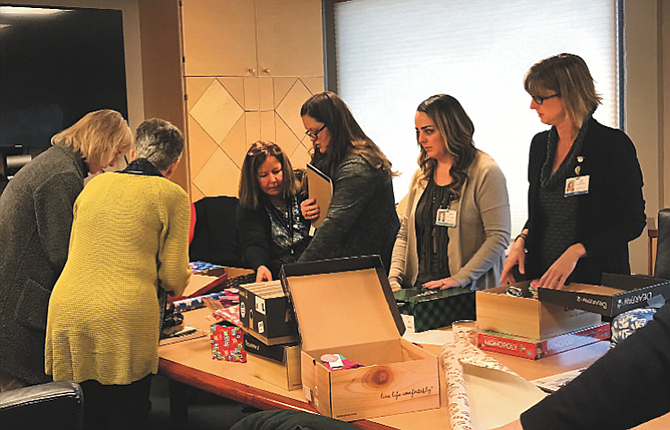 After a holiday lunch on Dec. 7, physicians and health care providers at Mid-Columbia Medical Center wrap gifts for distribution to needy families. Involved in the outreach effort are, from left, Dr. Sara McCaffrey, Dr. Sonia Chuemann, Becky Raulston, Katie Kelly, Tasha Sandoval and Lisa Sosa.