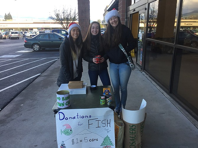 LEADERSHIP members Kiki Hosaka, left, a junior, and seniors Morgan Graves and Abby Walker greet food bank donors at Rosauers on Christmas Eve. The food bank drive is serious business but also a fun competition for HRVHS students. The top four classes bringing in the most donations win prizes, and the student body will enjoy perks if they pass the levels from 60,000 to 100,000, including staff members' agreement to tattoos.