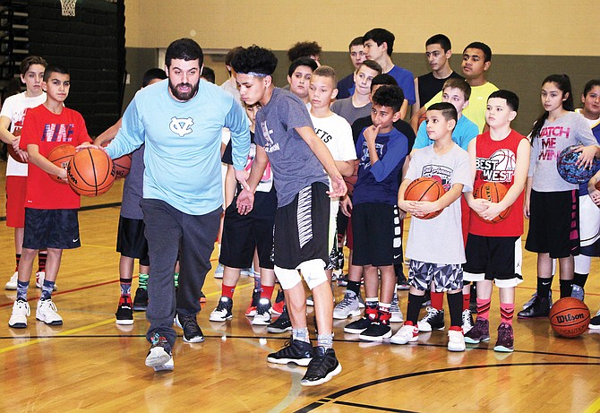 509 Insanity basketball trainer Bryan Edwards drives past Isaiah Isquierdo, 13, of Harrison Middle School, during a camp yesterday at Sierra Vista Middle School.