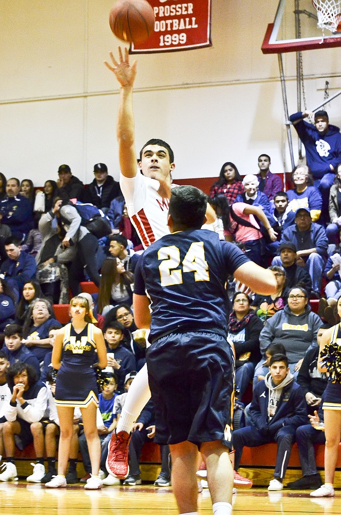 Prosser's Angel Rivera shoots over the head of Antwaan Acosta of Wapato in a 2-point attempt last night.