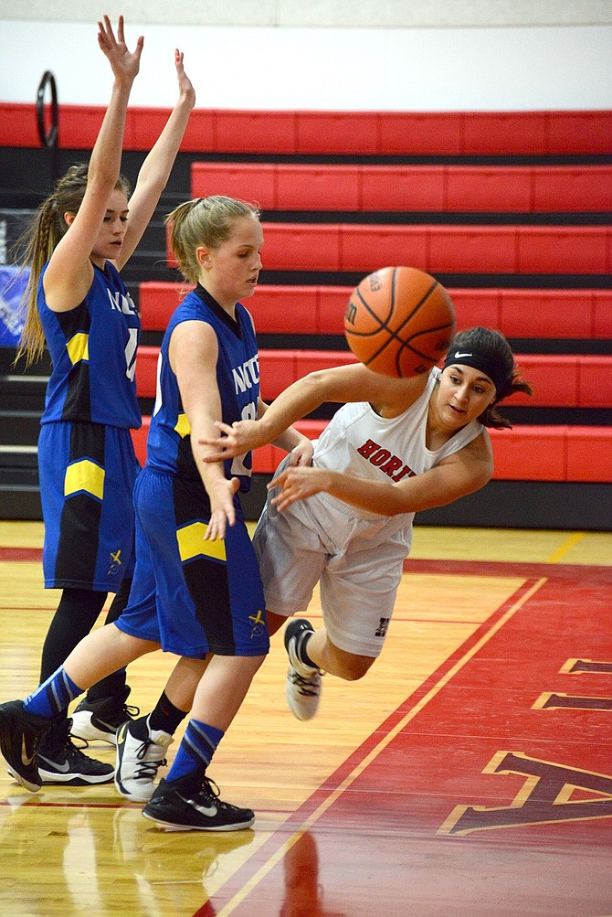 HALEY BECNEL (white jersey) passes the ball as she's crowded out at the baseline in Tuesday's game with North Clackamas.