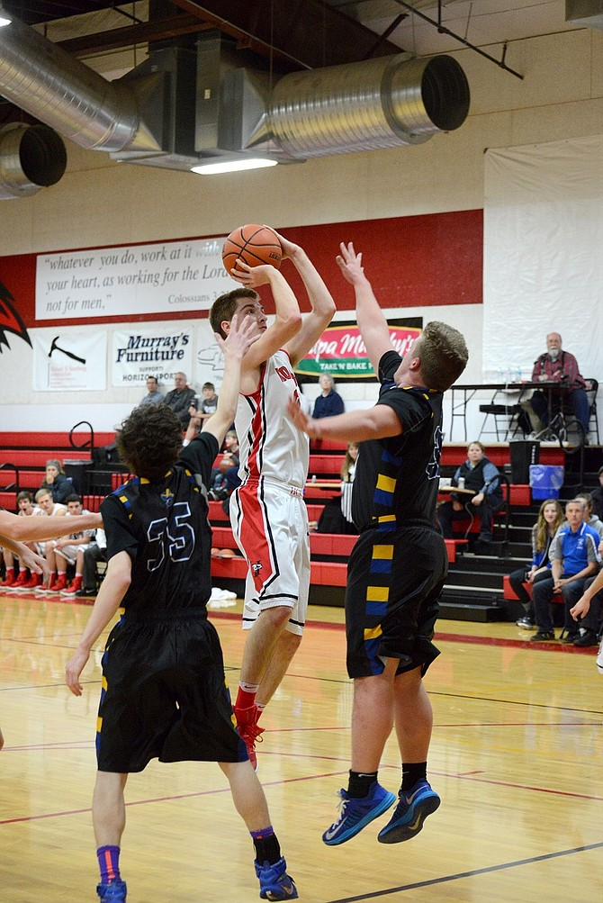 IAN WALKER (left) evades two Saints and pulls up for a jump shot during Tuesday's game against North Clackamas.