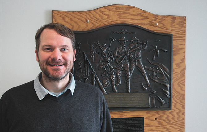 Sgt. 1st Class Ben Hall, who served five years as Readiness NCO at the Fort Dalles Readiness Center, poses next to a bronze wall plaque honoring the Oregon National Guard at the facility.