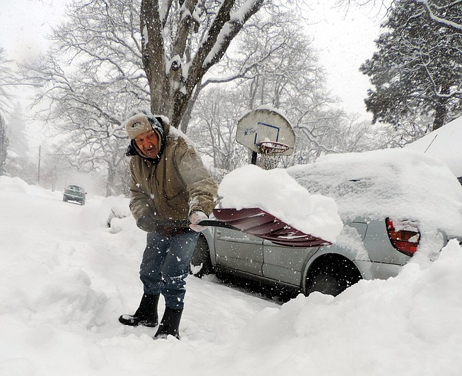 """Richard Logan, 86, shovels in front of his house on east Montello Monday. """"Not everyone shovels their walk or in front of their place — it helps the mailman and other people,"""" he said."""