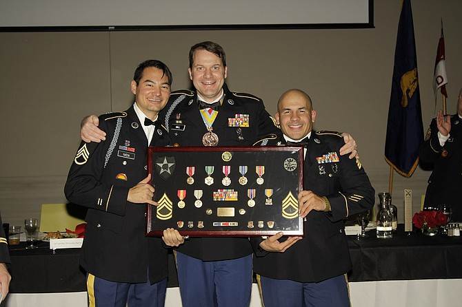 GOING AWAY GIFT: At the unit's Christmas party on Dec. 3, 2016, Staff Sgt. Anthony Iven (left) and Sgt. Clint Graeber (right) presented Sgt. 1st Class Ben Hall with a framed display of the medals and citations Hall earned while serving in the military for more than 25 years.