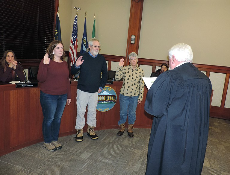 COUNCIL members Megan Saunders, left, Mark Zanmiller, and Kate McBride are sworn in Monday by Judge Will Carey at the start of the city council meeting.