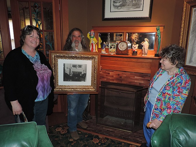 STEPHEN Datnoff holds the early-20th century photo of Simpson and Alice Williamson Copple in front of the fireplace. With him are Janice Willcocks, left, and Mary Anne Copple Willcocks. The knick-knacks are different but the mantel, fireplace and masonry are mostly unchanged. Datnoff stripped the white paint to reveal the woodwork on the mantel and unique two-pane mirror back.