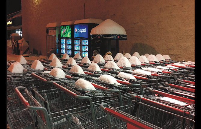 Deep snow brings out unexpected patterns, such as this series of peaks on rows of shopping carts stowed outside Kmart. Snow has  been on the ground continuously since early December, and a large snowstorm hit the area Saturday. This picture was taken Sunday evening.