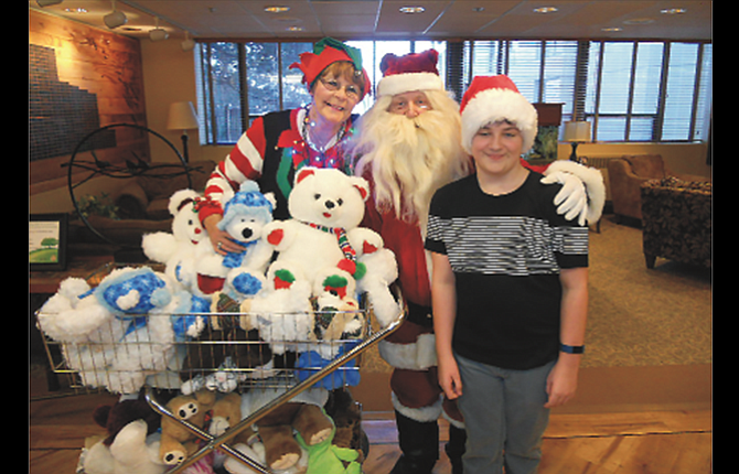 Santa Claus (Steve Wray) works with volunteers Sharon Hull and Hayden Wray to deliver 39 stuffed animals at MCMC on Christmas Eve.