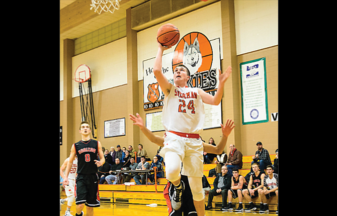 Sherman senior Max Martin glides to the rim for a one-handed layup during Friday's Big Sky Conference basketball game played against Horizon Christian. Saturday, the No. 5 Huskies had five players hit double figures in a 78-25 victory.