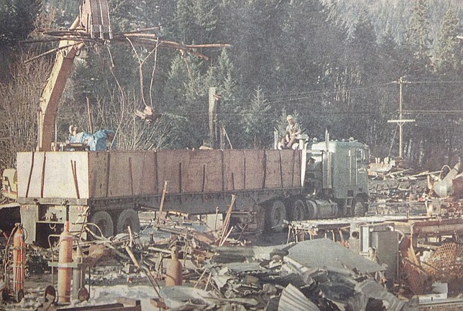January 11, 1997 — Workers load scrap Thursday as part of the demolition project at Dee Forest Products plant, destroyed last November by fire. Dee officials are due to decide on rebuilding plans by the end of the month. Thomas Bennett photo.