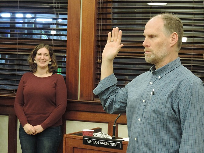 Mayor Paul Blackburn, elected to a second term in the November General Election, takes the oath of office Monday prior to the City Council meeting. Looking on is the council's newest member, Megan Saunders, who also took the oath from Judge Will Carey