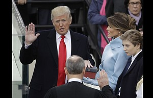 Donald Trump is sworn in as the 45th president of the United States by Chief Justice John Roberts as Melania Trump and son Barron Trump look on during Friday's Presidential Inauguration at the U.S. Capitol in Washington.