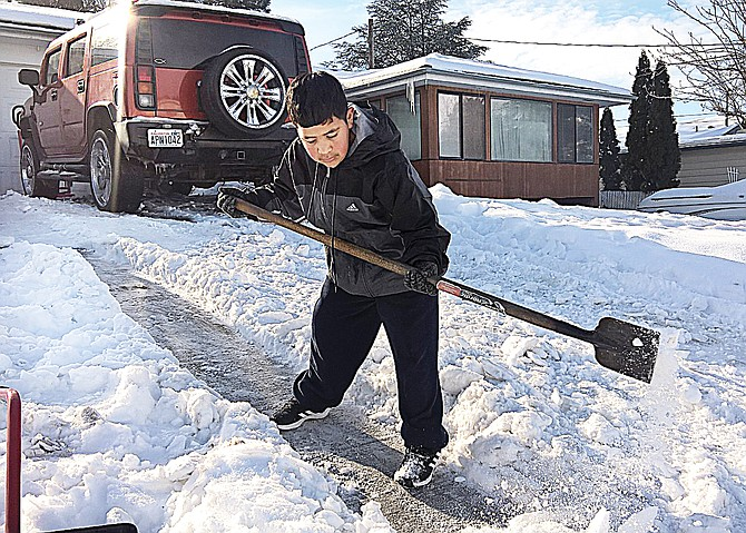Chris Villalobos of Sunnyside digs out his family's driveway Saturday, on his 15th birthday, during a sun break in the Lower Yakima Valley's series of snow and ice storms.