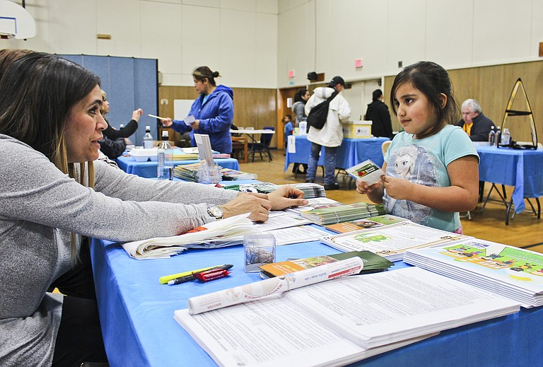 Sunnyside Community Service office worker Shannon Williams gives Eva Belan Trujillo, 5, coloring materials during Project Homeless Connect's resource fair yesterday in St. Joseph Church's parish hall.