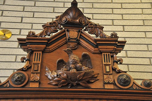 Hand carved at the top of the grandfather clock is a mother eagle sheltering a nest of her young.