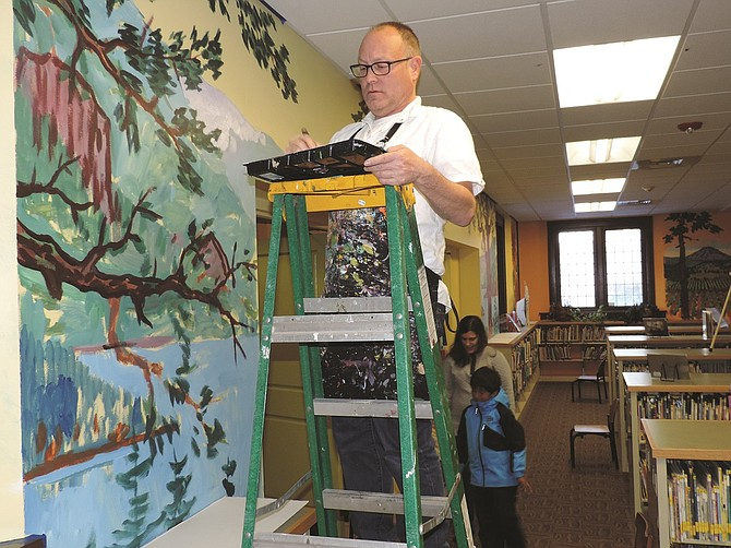 ARTIST Mark Nilsson paints a Gorge scene in the children's section of the Hood River Library.