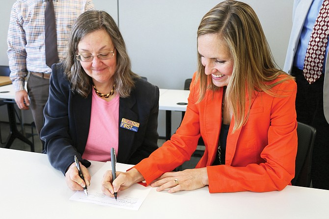 Heritage University's Laurie Fathe, left, and WSU's Jennifer Robinson sign two agreements last week to launch a pharmacy program partnership.