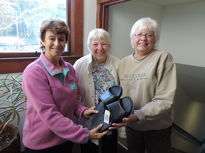 SHELTER SERVICES committee member Bev Carpenter, center, presents footwear to be used by guests to Steering Committee Co-directors Jan Miller, right, and Carole Dearhart.