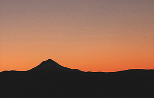 Mount Hood is sillouetted against the setting sun in this view from Tygh Ridge south of Dufur.