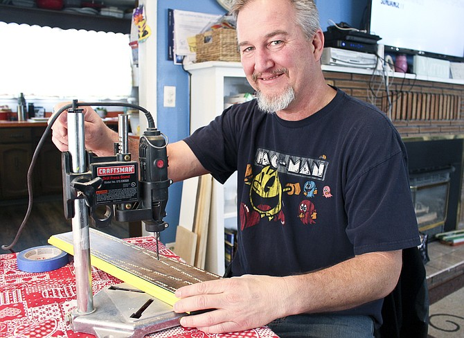 James Morrow is not only a cribbage life master, having won six club championships, he is also a master cribbage board maker. Many of the trophy boards presented at area tournaments are made at his Sunnyside kitchen table. He is pictured at work on a board.