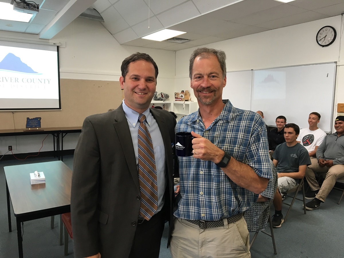 RICH TRUAX, right, accepts a congratulatory coffee mug from district Supt. Dan Goldman. Truax has served on Local Option and bond committees, and budget committee.
