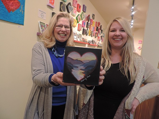 "Dozens of miniature hearts are on display and for sale, $15 apiece, at Columbia Center for the Arts. The panels are the result of the ""Community Paint Out,"" attended Jan. 21 by dozens of painters who put onto canvas their renditions of hearts, in association with the Heart and Soul exhibit. Sponsor Mary Haskins, above left, purchased a Gorge-inspired work by Audrey Bernhardt, who is gallery assistant at CCA.  Haskins was named CCA board president this week."