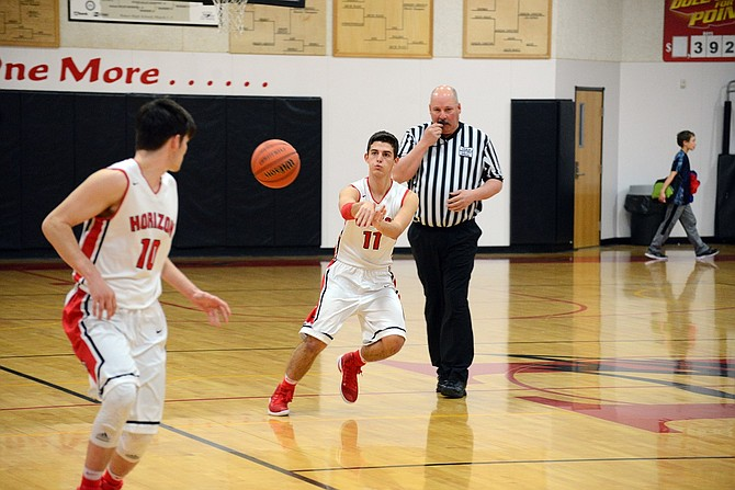 ETHAN EVANS (right, No. 11) passes the ball to Luke Holste during Tuesday's game with Condon/Wheeler.