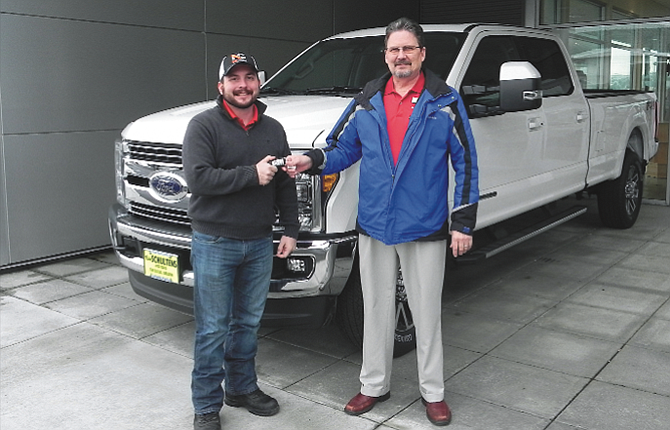 Brandon Kuehnl, left, accepts the keys to his new pickup from David Land of Ray Schulten's Motors.