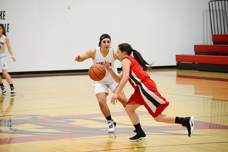 Haley Becnel (white jersey) hounds Rangers guard Alexus Outlaw.