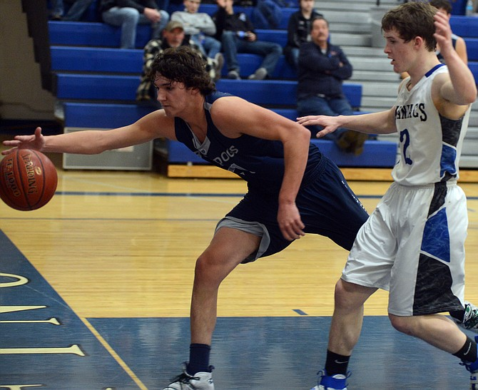 Grangeville senior Patrick Schumacher almost made the save on this loose ball, and almost saved the Feb. 6 game at Orofino for the Bulldogs with a three-pointer that sent the contest to overtime. Orofino's Garrison Bretz (right) helped lift the Maniacs to a 60-59 win.