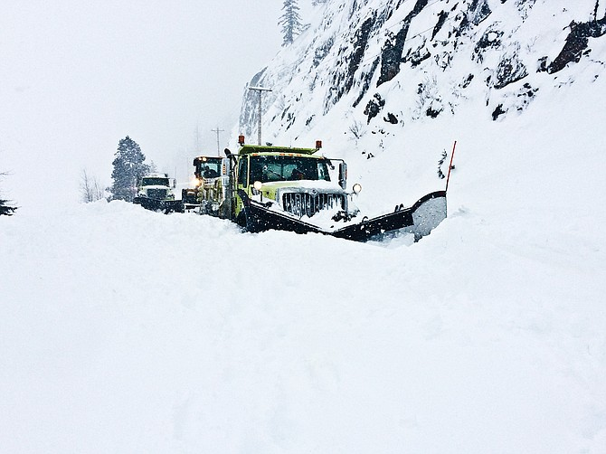 State snowplows struggle with snow in White Pass yesterday. Snow slides were so severe that one partially buried one of the plows.