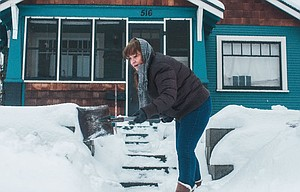 Susan Seeley scrapes and shovels the snow from the steps and sidewalk of her home Wednesday afternoon at 11th and Trevitt in The Dalles.