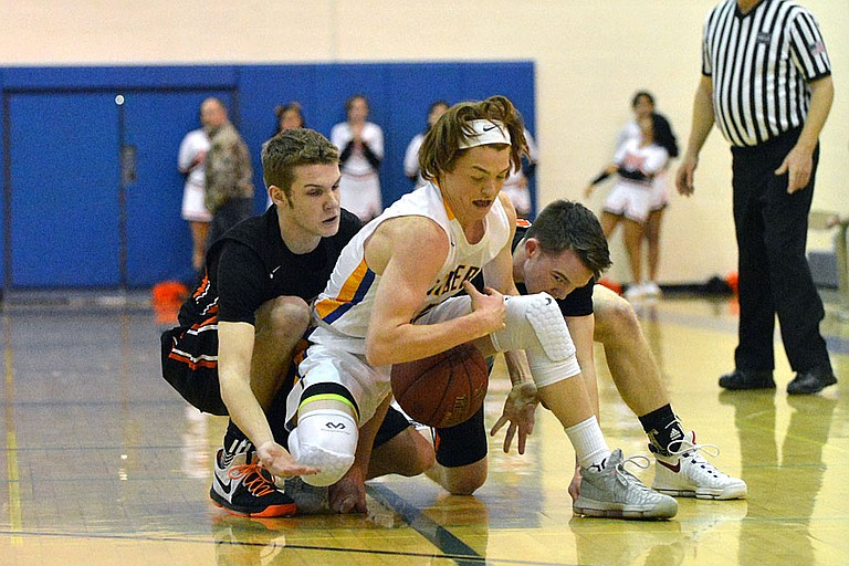 Bridgeport plays fight for a loose ball with Tonasket's Brayden Landdeck in a Wednesday 2B boys district game in Tonasket.