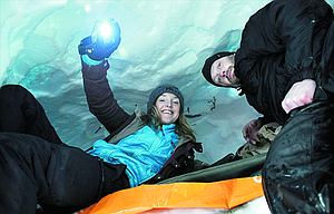 Lexi Nelson and Shannon Lavada check out the newly carved snow cave they built near Lookout Pass, Idaho, Jan. 28, during an overnight snowshoeing trek with the Spokane Mountaineers.