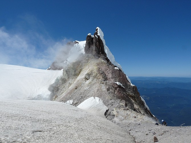 CRATER ROCK at the summit of Mount Hood will be one of four sites to get new volcano monitoring equipment, according to plans by USGS. In this 2011 photo, hydrologist Steve Ingebritsen stands near a potential site.