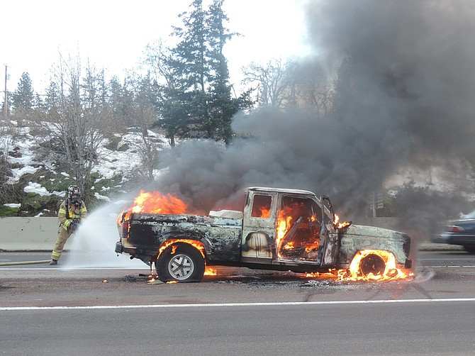 Hood River Fire Department's Adam Wheat applies water to a vehicle engulfed in flames Sunday afternoon on the westbound exit 62 on-ramp to Interstate 84.
