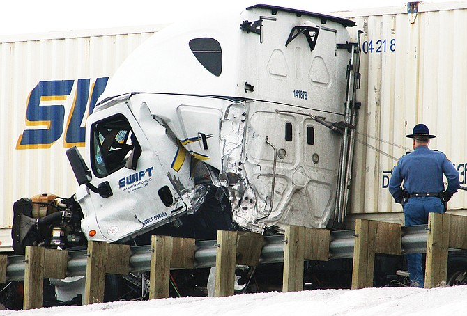 A Washington State Patrol trooper looks over the damage to a Swift Transportation Co. truck that jack-knifed early yesterday morning and came to rest against a guardrail near the Luther Road overpass of Interstate 82.