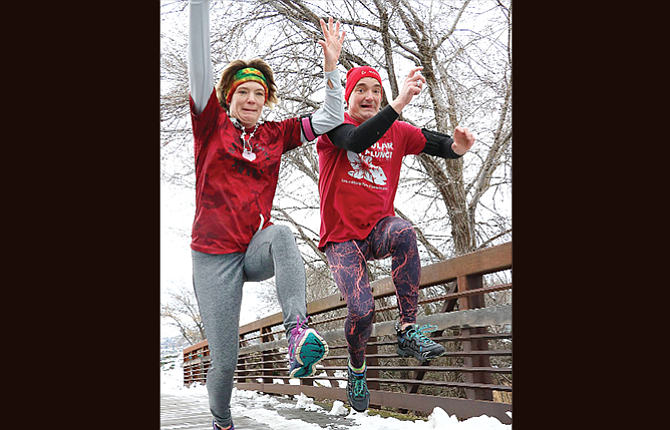 The Goldendale tandem of Cindy Berkshire, on left, and Shane Thompson jump for joy while running in Saturday's 10th annual Valentine's Day Trail Event.