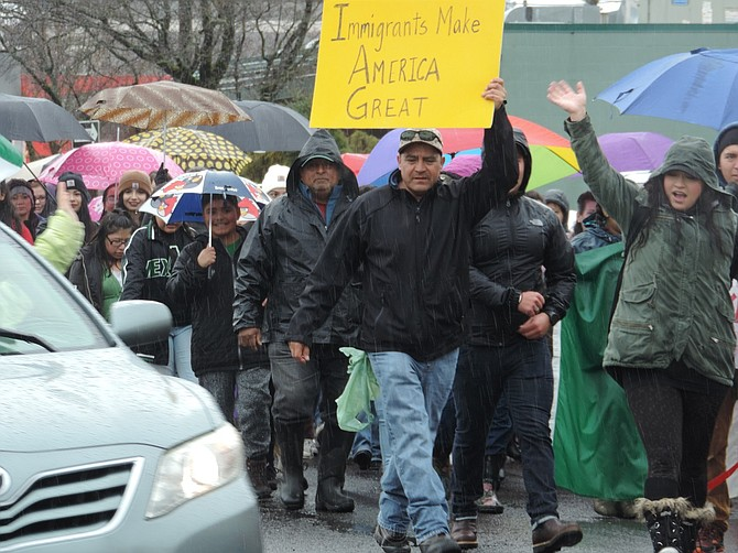 MARCHERS fill up one lane of 12th Street as they make their way south in the rain on Thursday. People of all ages, including 40 or so Anglos, joined the march.