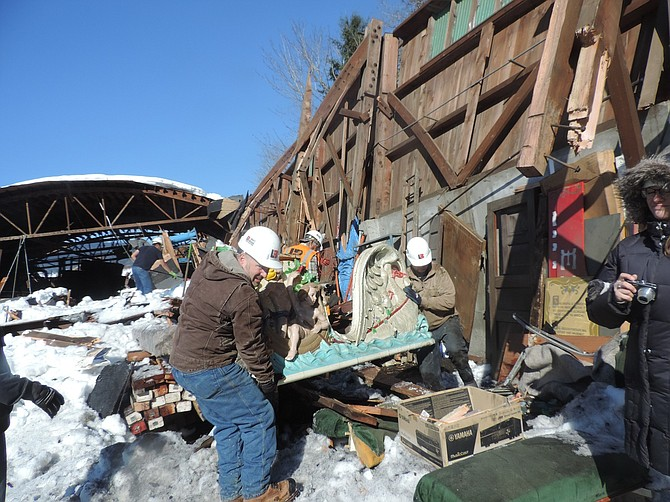 Building owner Brad Perron, left, and friends salvage parts of a 110-year-old Philadelphia-made carousel from the wreckage of Perron's storage building in Dee on Monday.