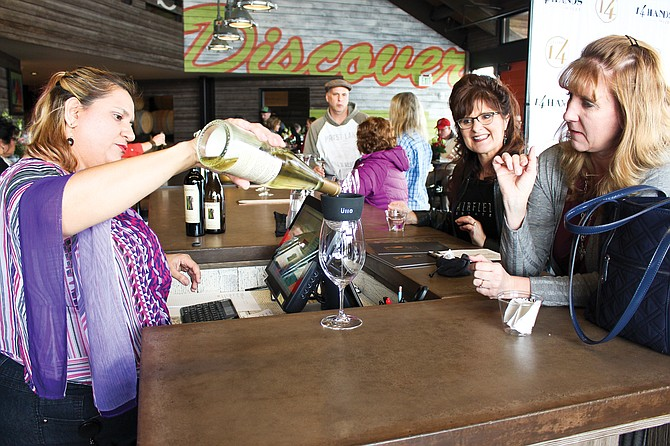 Tasting room server Marcelina Alvares pours a 14 Hands Winery Riesling for Crystal Morfield of Bickleton on Saturday. Morfield used a filter to remove sulfites so she could drink the wine. Also pictured to Morfield's left is Susan Powers.